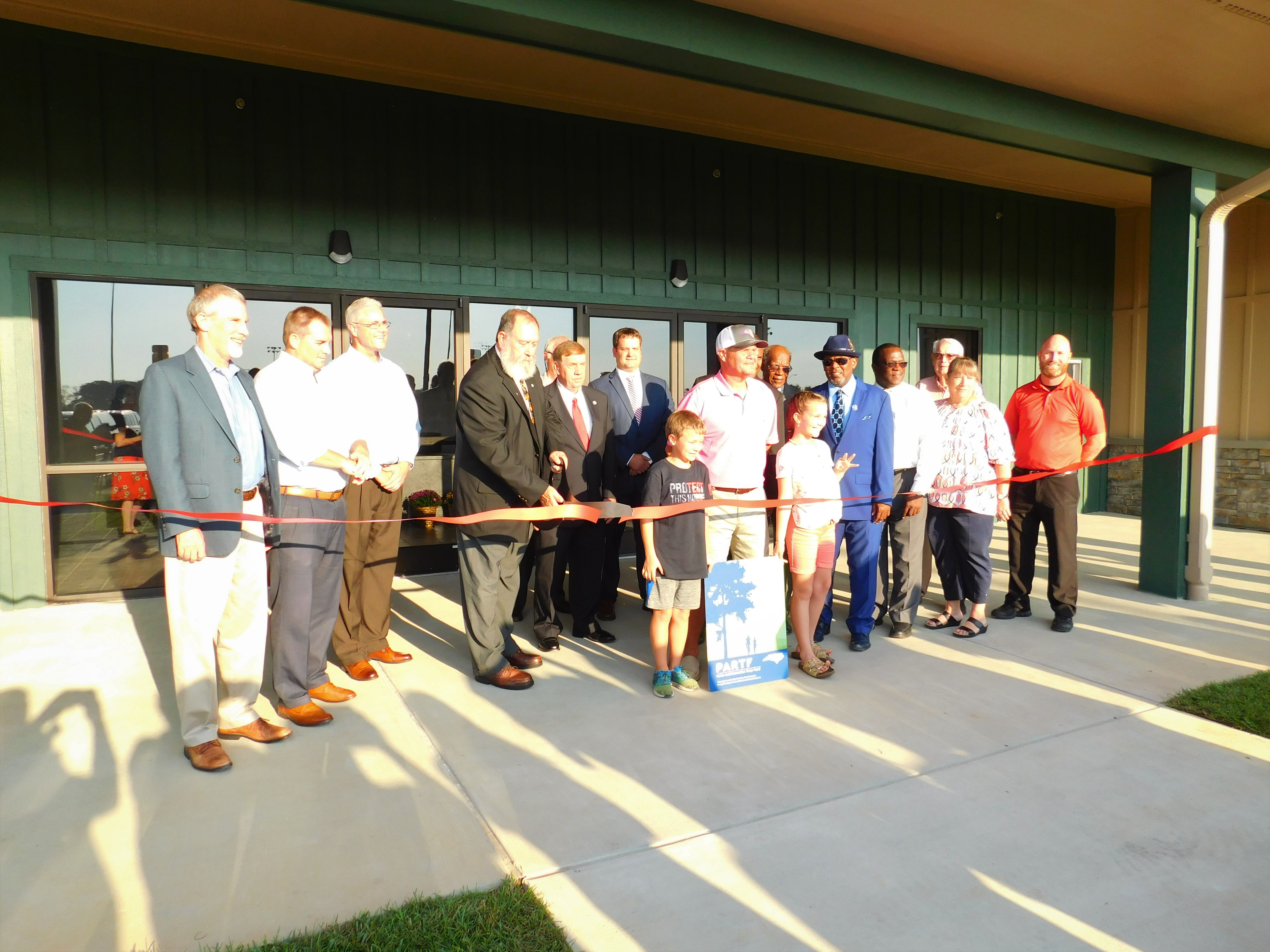 Man cutting ribbon at opening of Greene county wellness center
